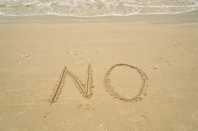 ビーチの砂浜に描いたNOという文字
