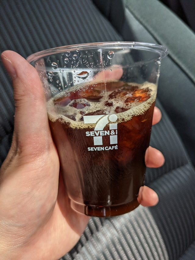 左手に持ったアイスコーヒーのカップ